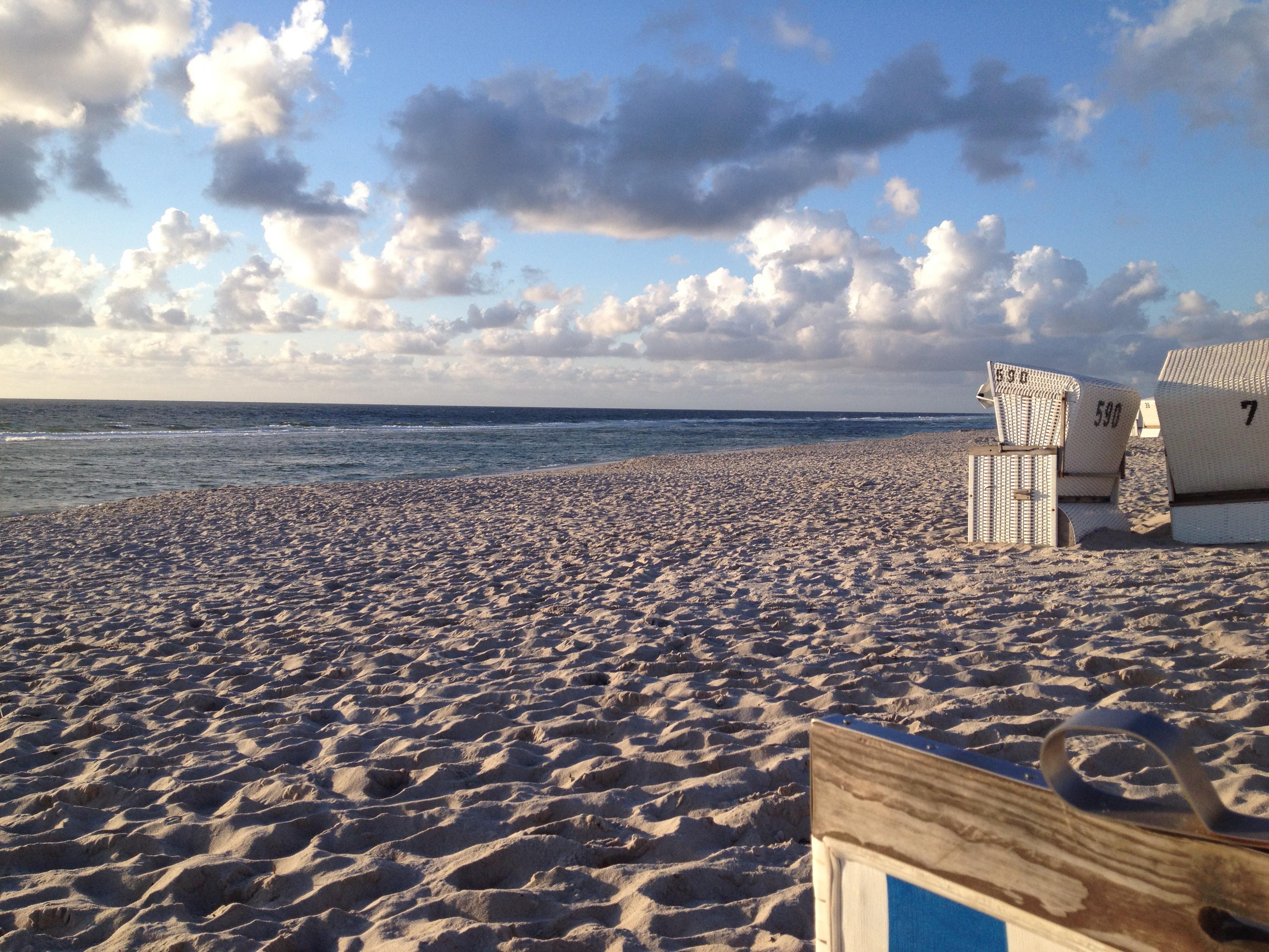 Strand mit weissen Strandkörben und schäfchen Wolken