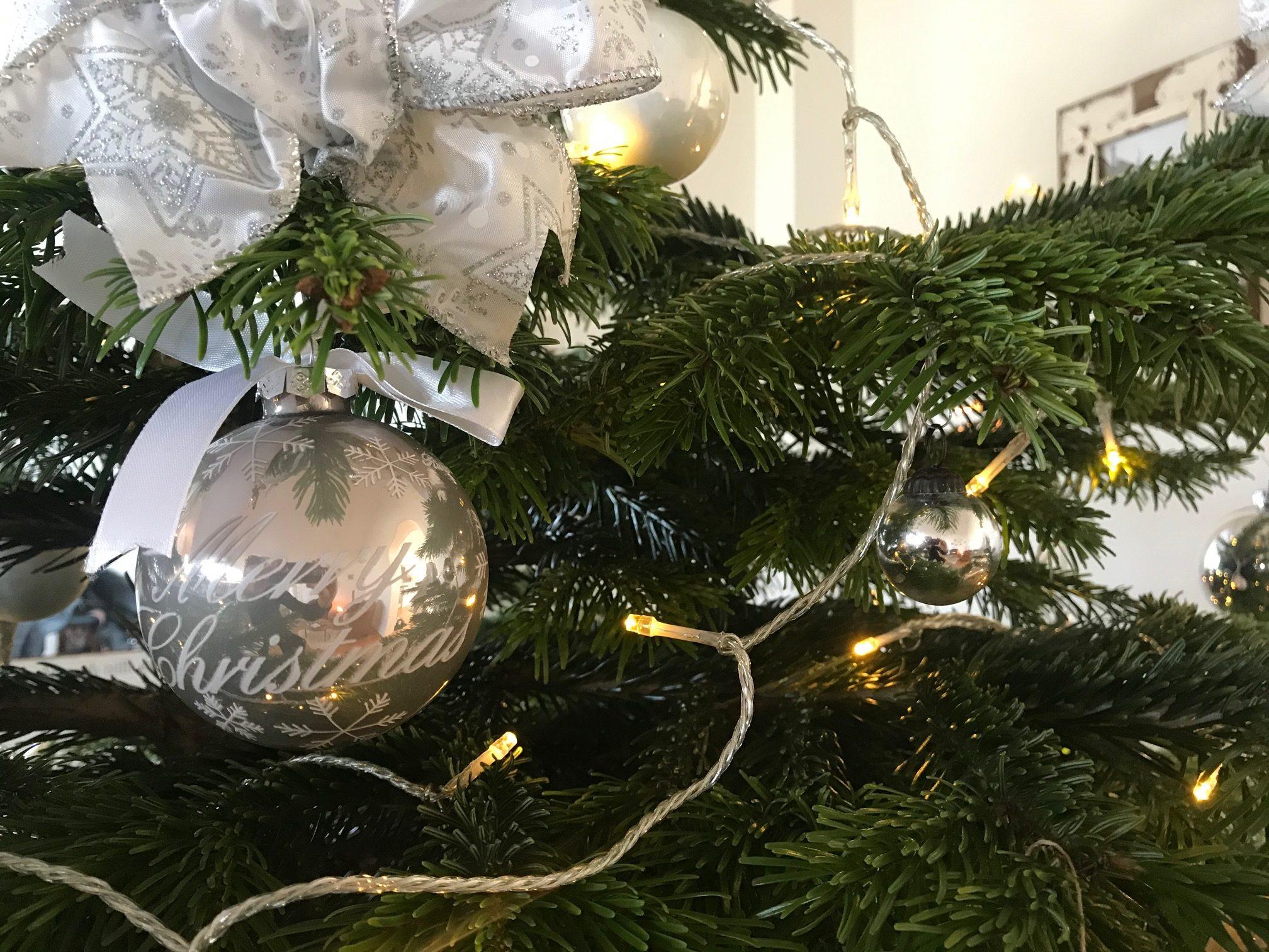 silberne Weihnachtskugeln am Tannenbaum mit Lichterkette